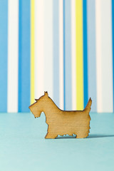 Wooden icon of dog on blue striped background