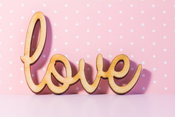 Wooden Love inscription on pink background