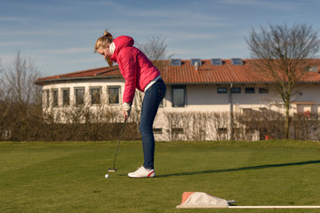 Junge Golferin spielt einen Putt auf dem Grün zum Loch