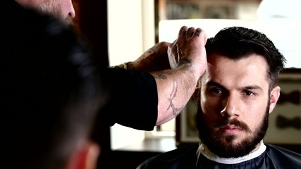 Barber performs a haircut with scissors and combs his client