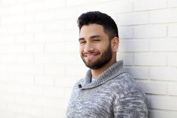 Plano medio de joven con barba sonriendo