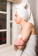 young woman looking out of a window after a shower.