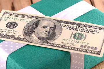 Holiday bonus.  american money on green gift box