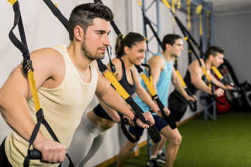 People training at elastic rope in gym