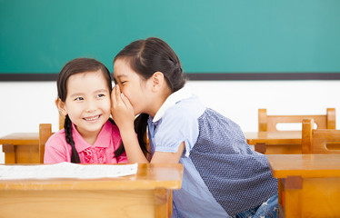 little girls whispering and sharing a secret  in classroom