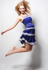 young happy woman in blue dress jumping