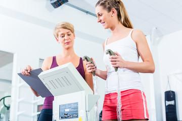 Trainer mit Körperfettwaage im Fitnesscenter