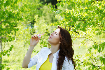 girl blow bubbles in spring forest