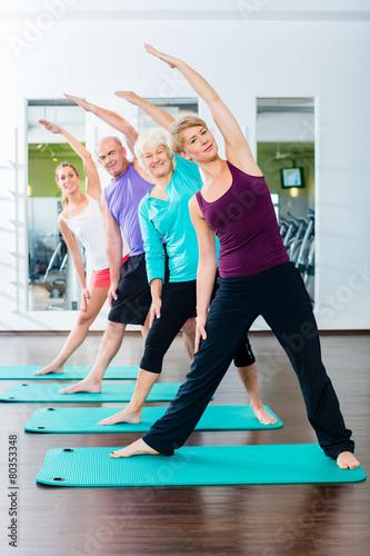 Leinwanddruck Bild Junge und alte Leute beim Gymnastik Training