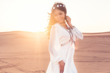 Beautiful woman standing in desert sunset