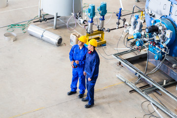 Two workers in industrial factory discussing