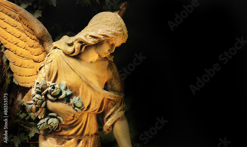 Tuinposter Standbeeld golden angel in the sunlight (antique statue)