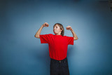 The boy, a teenager in red t-shirt shows the strength poster