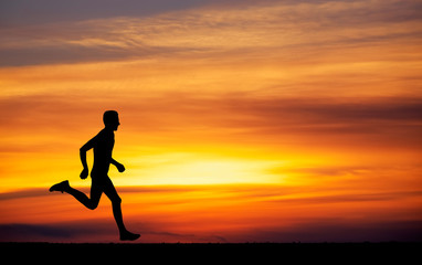 Silhouette of running man against the colorful sky.