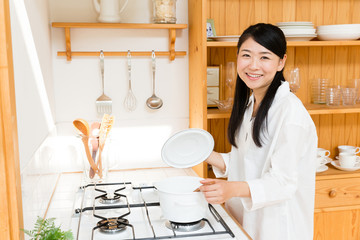 young asian woman cooking image