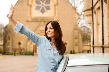 young woman waving out of car window