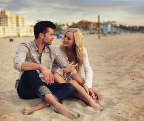 couple sitting in the sand and talking on beach