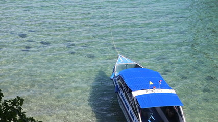 motor tourist speed boat tied up at coast of azure sea