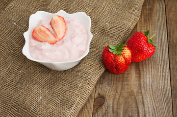 Fresh strawberry with yogurt in white bowl on wooden background.
