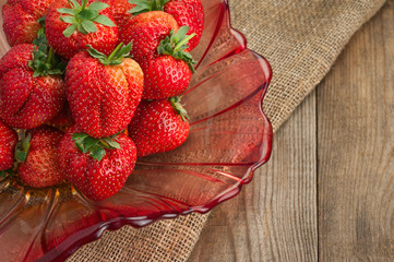 Fresh ripe strawberries in glass bowl on wooden background.