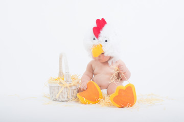 Baby in a costume of rooster sitting in a scattered hay grabbing