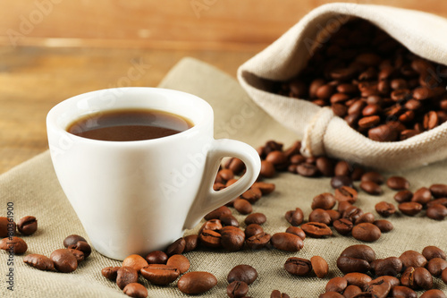 Canvas Cafe Cup of coffee with beans on rustic wooden background