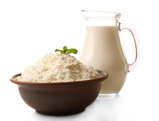 Glass jug of milk and clay bowl of cottage cheese isolated