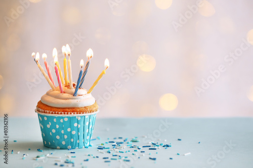 Tuinposter Eten Delicious birthday cupcake on table on light background