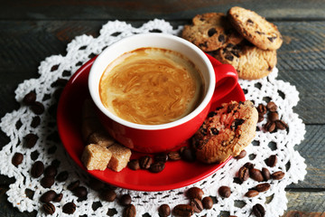 Cup of coffee and tasty cookies on wooden background