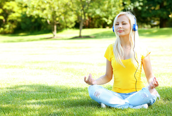 Blonde Woman with Headphone Meditating Outdoor. Student Girl