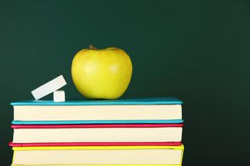 Books, apple and chalk on blackboard background