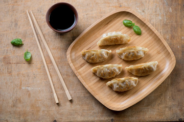 Bamboo tray with gyoza dumplings and dip sauce, view from above