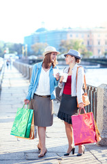 Two beautiful girls with shopping bags and cup of coffee