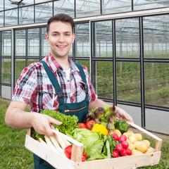 Lachender Landwirt mit Gemüse vor seinem Gewächshaus