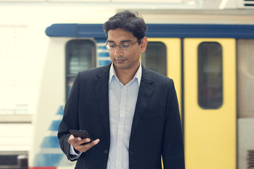 Asian Indian businessman texting using smartphone while waiting