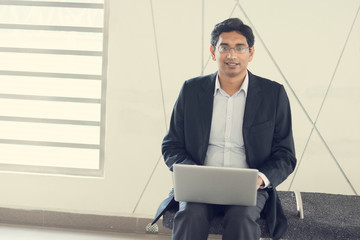 Asian Indian businessman using laptop computer while waiting tra