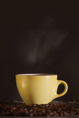 yellow Cup with coffee on a dark background