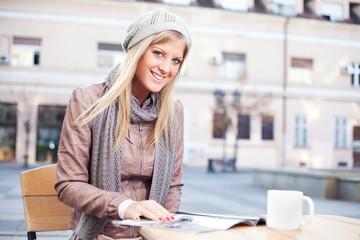 Happy girl reading magazine in a sidewalk cafe