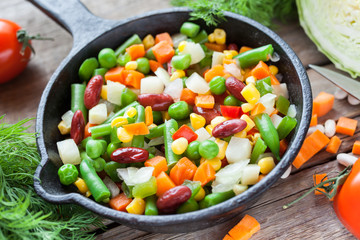 Mixed vegetables in retro frying pan and ingredients on wooden r
