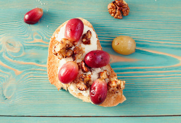 sweet toast with red grape, ricotta, walnut on blue table