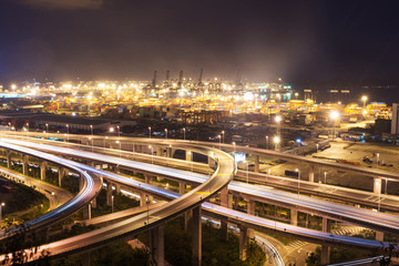 Traffic on elevated expressway and illuminated container wharf.