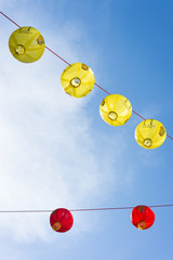 Red and yellow Chinese lanterns with blue sky in the background