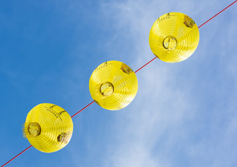 View from below of three yellow Chinese lanterns with blue sky