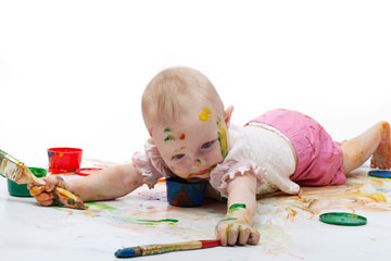 little girl soiled by bright paints lies