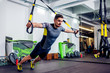 Crossfit instructor at the gym doing TRX Excersise - 80372381