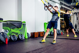 Fototapety Crossfit instructor at the gym doing TRX Excersise