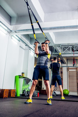 Crossfit instructor at the gym doing TRX Excersise
