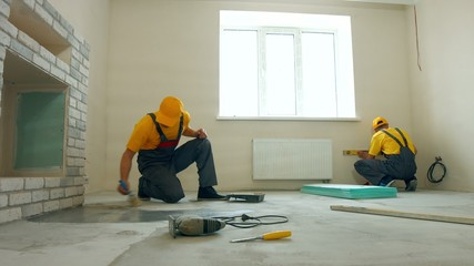 Priming floor in a large house. Workers insulated floor.