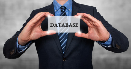 Businessman holds white card with Database sign. Stock Photo