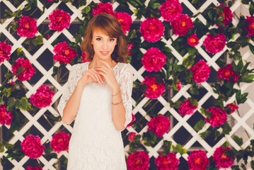 positive girl in elegant white dress on a background of flowers